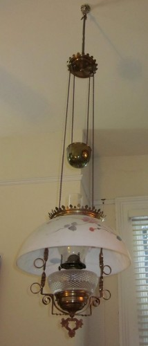Early/mid 19th century height adjustable pendant oil lamp. Brass fixtures, painted glass shade. Chain and counterweight allow it to raised and lowered. Now used as paraffin lamp; originally probably intended to be fueled with whale oil.via Wikipedia, CC License.