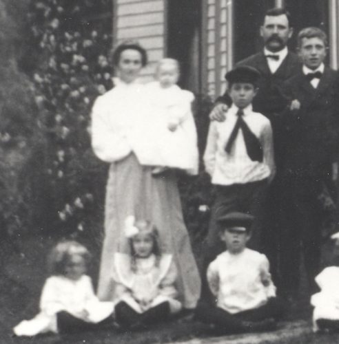 The family of Mary Jane (Roberts) Blount, 1900. Standing, from left, Mary Jane (Mollie J) (Roberts) Blount, baby Bernice Blount, Samuel Harvey Blount with hat and tie, and his father Samuel H. Blount, and Harry R. Blount. Seated on ground from left: Florence Blount, Helen J. Blount, Harold M. Blount. Cropped from a larger family photo.
